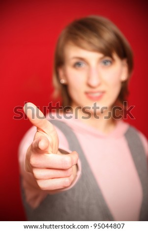 young woman in front of red background pointing at you (focus on hand) - stock photo