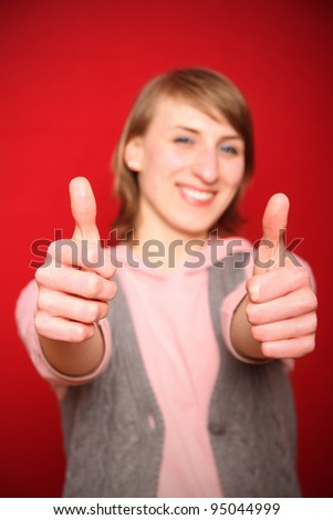 young woman in front of red background really impressed and giving both thumbs up (focus on hands in the foreground) - stock photo