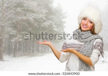 Young woman in fur hat shows welcome gesture at snowy forest - stock photo