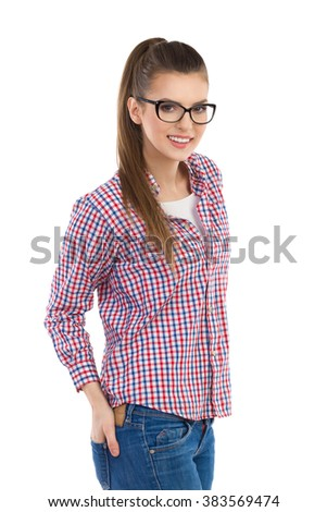 Young woman in glasses and lumberjack shirt posing and holding hand in back pocket. Three quarter length length studio shot isolated on white. - stock photo