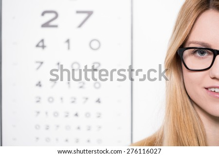 Young woman in glasses in front of snellen chart