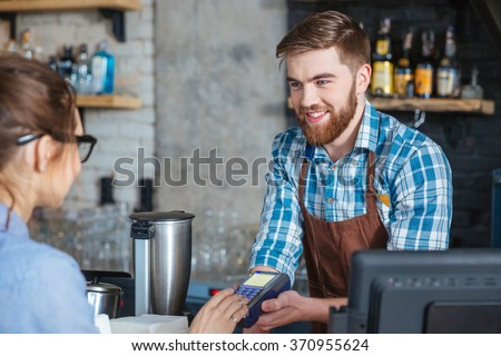 Young woman in glasses paying by credit card and entering pin code on reader holded by smiling bearded barista in cafe - stock photo
