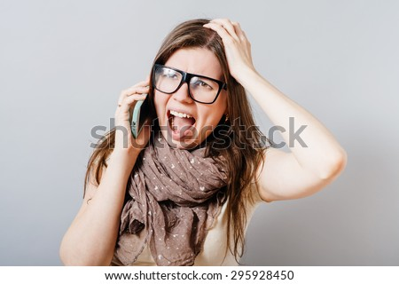 Young woman in glasses shouts on the phone. On a gray background.