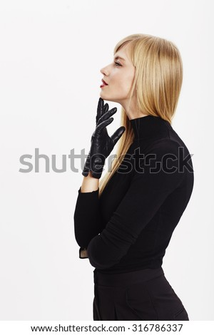 Young woman in gloves thinking in white studio