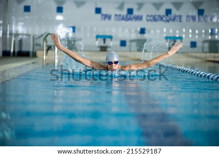 Young woman in goggles and cap swimming butterfly stroke style in the blue water indoor race pool
