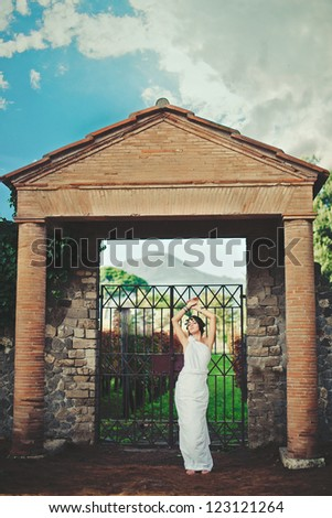 Young woman in Greek style  near old gate - stock photo
