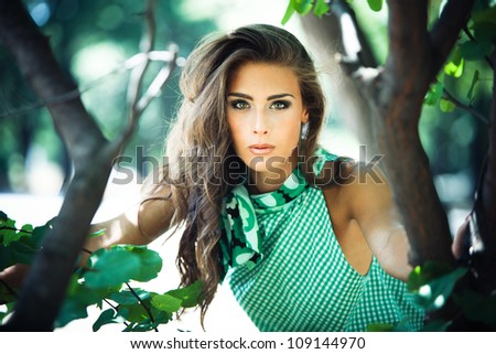 young woman in green dress fashion  shot in the wood summer day