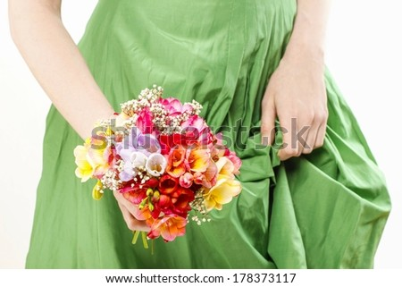Young woman in green dress holding bouquet of colorful freesia flowers
