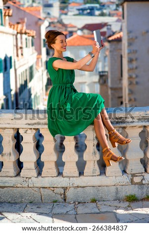 Young woman in green dress using digital tablet in Dubrovnik old city center