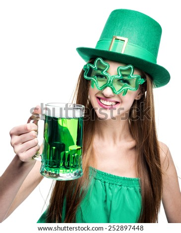 young woman in green hat and shamrock eyeglasses is drinking green beer from a mug - stock photo