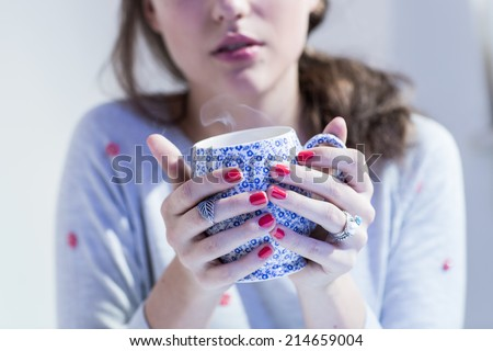 Young woman in grey sweater with red spots holding decorative cup of tea or coffee with smoke. Color toned image. Cold filter. - stock photo