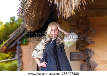 Young woman in grey ukrainian national costume near old historic house - stock photo