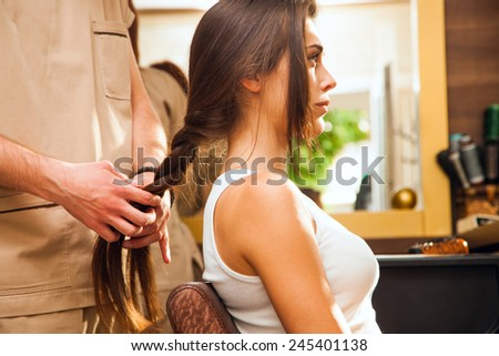 young woman in hair salon making braid of hair - stock photo