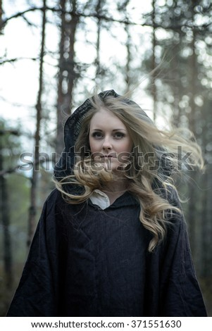 Young woman in Halloween witch costume in the autumn forest