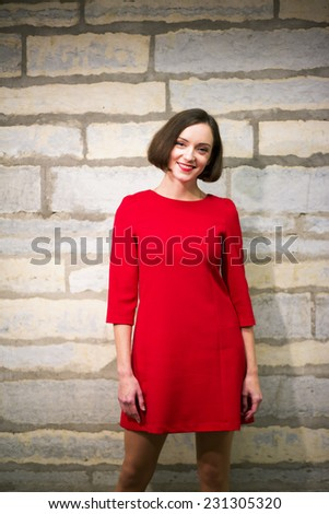Young woman in hallway stand on limestone wall - stock photo