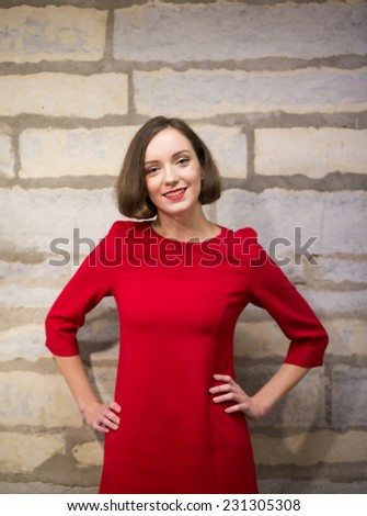 Young woman in hallway with hands on hips - stock photo