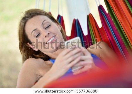 young woman in hammock connected with smartphone - stock photo