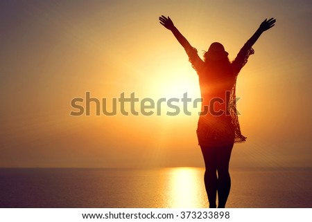 Young woman in hat and cute summer dress standing on the stone, looking at sunset over the sea - stock photo