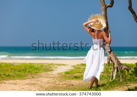 Young woman in hat and white dress near the ocean. Back view - stock photo