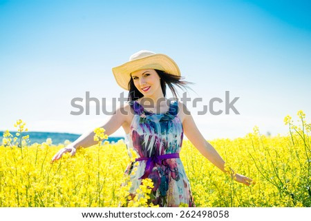 Young woman in hat having fun in yellow rapeseed field - blue sky in background - stock photo