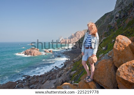 Young woman in hat on Cabo da Roca rocks, the western point of Europe - Portugal - stock photo