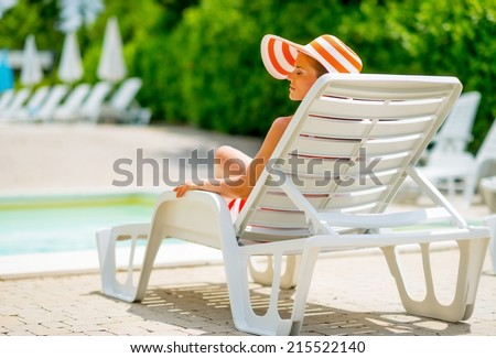Young woman in hat sitting on sunbed. rear view