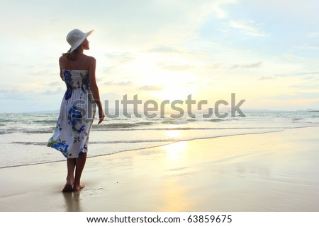 Young woman in hat standing on sand and looking to a sky - stock photo