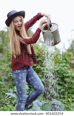 Young woman in hat watering cabbage in farm garden