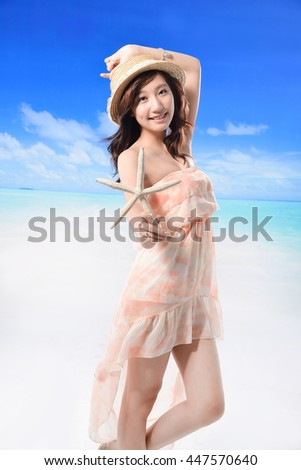 Young woman in hat with starfish standing on beach - stock photo