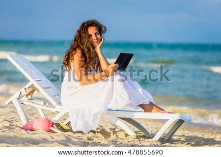 Young woman in hat with tablet pc at the beach. girl sitting on a deck chair with the tablet