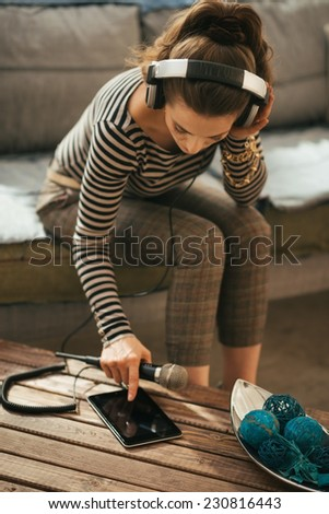 Young woman in headphones with microphone using tablet pc