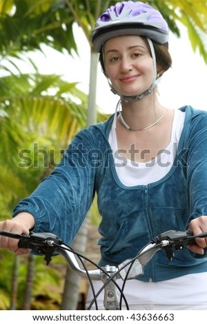 Young woman in helmet biking in the city