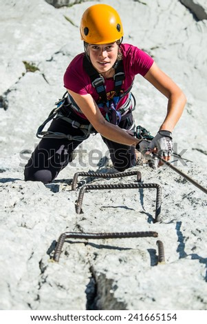 Young woman in helmet climbing via ferrata - stock photo