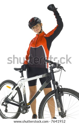 Young woman in helmet, standing with hand up next to mountain bike. Smiling and looking at camera. White background, front view - stock photo