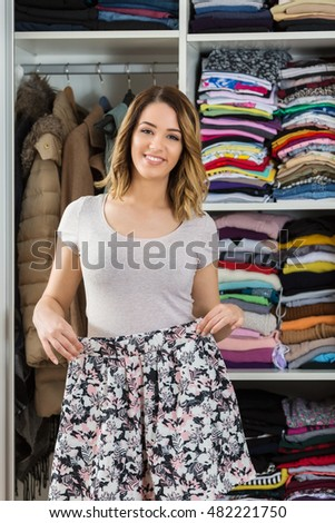 Young woman in her closet choosing which skirt to wear.
