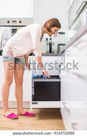 Young woman in her lovely, modern kitchen - stock photo