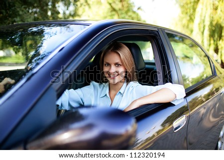 Young woman in her new car smiling. - stock photo
