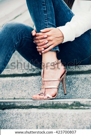 young woman in high heel shoes and blue jeans on stairs outdoor shot