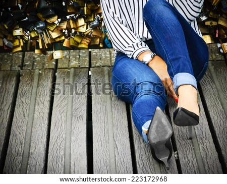 Young woman in high heel shoes and with red manicure sitting on Love locks bridge in Paris. - stock photo