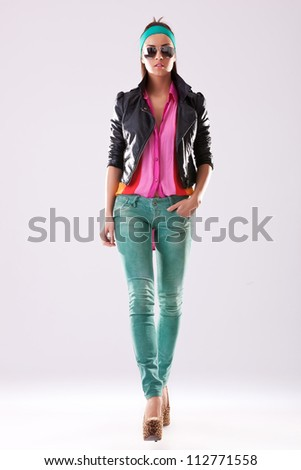 young woman in high heels and casual clothes walking towards the camera - stock photo