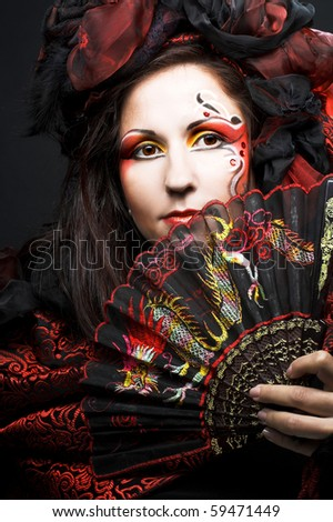 Young woman in hispanic style with fan - stock photo