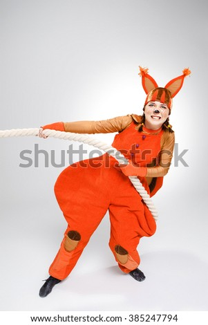 Young woman in image of red squirrel pulling a rope - stock photo