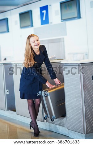 Young woman in international airport at check-in counter, putting her heavy luggage on the scales