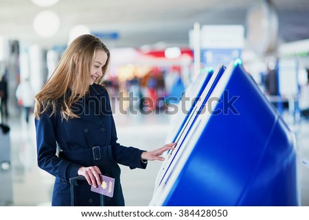 Young woman in international airport doing self check-in - stock photo