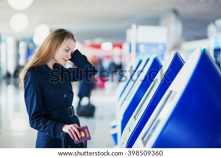 Young woman in international airport doing self check-in, stressed and concerned. Missed, delayed or canceled flight concept - stock photo