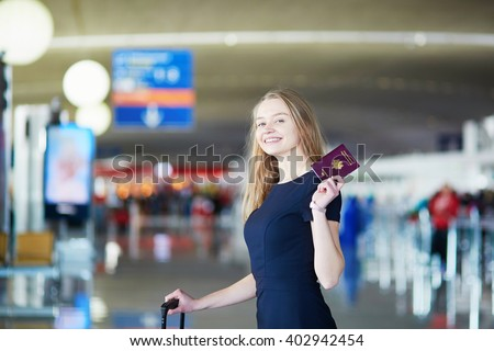 Young woman in international airport, holding French passport and looking happy - stock photo