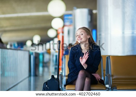 Young woman in international airport, waiting for her flight