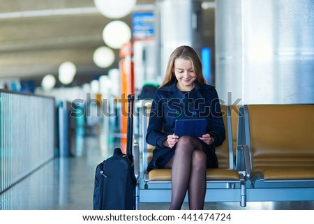 Young woman in international airport, waiting for her flight, using her tablet