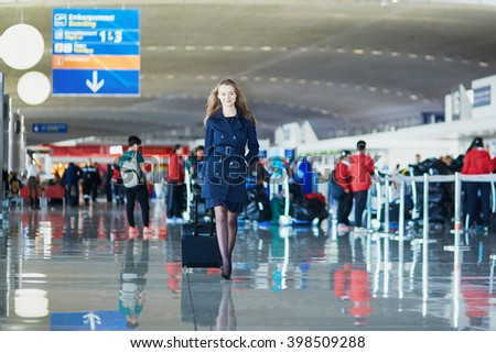 Young woman in international airport, walking with her luggage