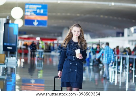 Young woman in international airport, walking with her luggage - stock photo